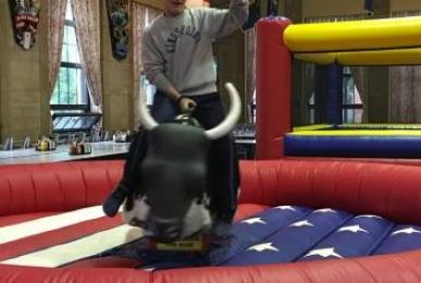 A student rides a mechanical bull.