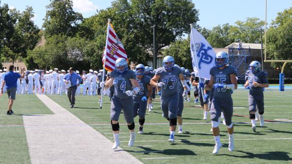 The men's football team runs their flags.